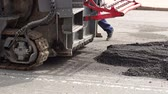 rozdrtit : Road works. Dismantling of asphalt pavement. A fragment of a trimming unit-track. A large industrial tractor cuts off the old asphalt. Slow motion.