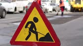 Roadworks signs on a street. Roadworks sign on a road. Road sign repair work and detour arrow. Repair work on the road. Workers laid new asphalt.