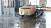 handy : The machine is covered with protective paper drives into the painting unit for painting the rear hood. Painting the car body at the service station. Stock Footage