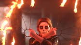 light eyes : Creepy bride with makeup on her face holding burning torches. Makeup for Halloween with a skull for girls. Portrait of a girl in a witch costume with fire and smoke.