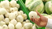 warenkorb : Close-up of a man chooses white onions in a supermarket. The family buys food and vegetables at the grocery store. Slow motion.