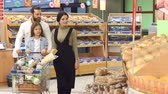 bakery shop : Beautiful young parents and their cute little daughter are smiling while choosing baking in the supermarket. Happy family with little girl picking bread from shelf in food store. Stock Footage