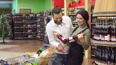expressando : Portrait of a young fashion couple in a supermarket or in a wine shop with a full cart of products. Bearded man with his wife in a liquor store, portrait. Slow motion. Choosing wine for dinner.