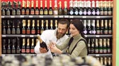 сочельник : Choosing wine for dinner. Happy fashionable couple choosing wine together while standing in wine store. Beautiful couple is smiling while choosing alcoholic beverage in the supermarket. Slow motion. Стоковые видеозаписи