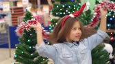 carrito de bebe : A little funny girl in the supermarket plays and dances with garlands on the background of decorated Christmas trees with flashing lights, she has a Hoop with a Santa hat on her head. Slow motion.