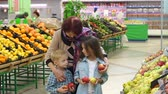 vnuk : Sweet kind grandmother with small children buy fresh apples in the supermarket. Happy family shopping at the grocery store. Dostupné videozáznamy