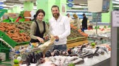 engaged : Beautiful young couple is choosing fish and smiling while doing shopping at the supermarket. Couple buying fish. Couple is choosing frozen seafood for dinner in the supermarket.