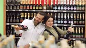 expressando : Portrait of a young fashion couple in a supermarket or in a wine shop. A young couple chooses champagne in a wine shop. Portrait. Slow motion. Choosing wine for dinner.