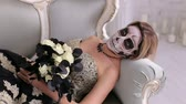 zlomenina : A creepy woman in a medieval dress and with makeup in the form of a skull lies on a retro sofa in an ancient castle. Day of the dead girl with sugar skull make-up. Halloween concept. Zombie. Top view