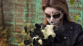 geist : A creepy bride with a bouquet of black flowers and make-up in the form of a skull stands against a rusty green fence. Woman dressed in costume cosplay horror dead bride or ghost on Halloween festival.