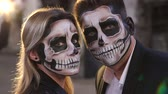 netvor : Couple in wedding clothes and with a terrible makeup for Halloween stand against a burning fire in the dark among the smoke. Halloween loving couple with skull make-up. Halloween or horror theme.