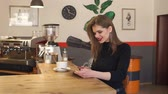 ruj : Young girl sitting in a coffee shop with a Cup of coffee and a tablet, she looks at the screen and smiles. Portrait of a happy smiling girl in a coffee shop with a fragrant cappuccino and a tablet. Stok Video