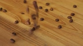 pours out : Barista pours out coffee beans from a bag on a wooden table in a coffee shop. Coffee beans slowly fall on the wooden table. Close-up of coffee beans on a wooden surface. Slow motion. Stock Footage