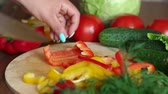 korken : Close-up of a woman cutting ripe juicy red pepper on a wooden Board, in the background are cucumbers and tomatoes. Videos