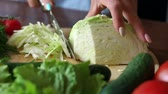 измельченный : Female hands chopped cabbage on wooden board, close-up. Chopping cabbage with a knife on cutting board.