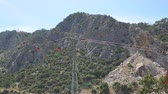 cabaña en el bosque : Cable car with red trailers on the background of the mountains. Antalya, Turkey. A cable car carries people to a high mountain. Funicular. Archivo de Video
