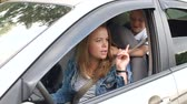 ignorieren : A little boy closes his mothers eyes while driving a car. Naughty child indulges in the car, he is not wearing seat belts and prevents his mother to drive the car. Danger in the car. Videos