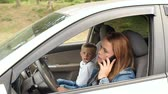 distraído : Irresponsible mother talking on the phone while sitting at the wheel of a car, a spoiled child sits nearby and prevents her mother from talking. Woman yells at a child in a car while talking on phone.