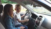 přijímač : Funny little boy sitting in his mothers arms at the wheel of the car, he turns on loud music and begins to dance. Slow motion. Portrait of a mother with a child in the car, fun during the trip.