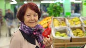 paketlenmiş : Good-looking senior woman holding red pepper, examining it with care, smiling while grocery shopping in supermarket, standing in front of boxes filled with fresh fruits and vegetables.