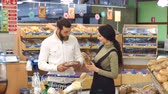 gündelik : Portrait of a young couple with a full trolley of products in the supermarket. Portrait of family shopping for groceries in supermarket together, while choosing fresh bread loaf in bakery department. Stok Video