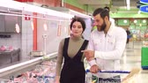 lednička : Food, sale, consumerism and people concept - happy couple with shopping cart buying meat at grocery store or supermarket. Positive smiling family couple choosing chilled meat in food store.