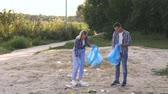 опрятный : Group of young volunteers picking up trash on the beach. Woman and man wearing gloves are cleaning the beach in the Park by the lake. Slow motion.