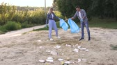 опрятный : Cheerful young people clean up garbage on the shore of a small lake in the Park at sunset. Slow motion. Group of people picking up trash in the park. Volunteer community service. Стоковые видеозаписи
