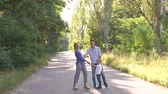dirigeants : A happy family with a young son walking along an empty road in the woods, they hold hands and laugh. Slow motion. Summer family trip.