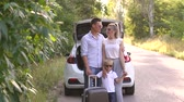 paketlenmiş : Portrait of a happy young family with a suitcase near the trunk of a car on an empty road in the woods. The family travels by car. Parents with son gather on summer holidays. Stok Video