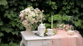 orchideen : Wedding decor. Vintage table with bouquets of flowers, tea set and transparent veil on the background of green leaves. Morning for bride. Videos