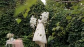 perle : Wedding dress hanging from gorgeous wedding arch covered in flowers. Beautiful wedding dress hanging in the green Park. Wedding decor for the bride.