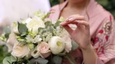 flower bed : Close-up of the bride holding her wedding bouquet, she gently touches the flowers.