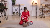 oso de peluche : A beautiful young woman plays with her son with a Teddy bear, they sit on the floor on a soft carpet. Portrait of mother and son at home. Theyre wearing red clothes.