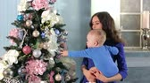 januari : Young beautiful mother in a blue dress holding her little son, they decorate the Christmas tree. Portrait of a mother with a newborn son near the decorated Christmas tree at home.