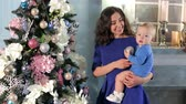 januari : Mom with a cute newborn son playing with Christmas tree toys, mom dressed in a blue dress and a child in a blue suit. Portrait of a happy child with his mother near the Christmas tree.