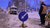 municipal services : Operating specialized snow removal equipment working on city streets after a heavy snowfall. Worker install warning road signs. Removing snow with plow. Stock Footage
