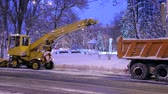 odstranění : Close-up process of working snow plow. Snow plow loads snow into the truck body. Special transport city cleans the road from snow.