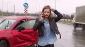 abschleppdienst : Portrait of a frightened girl on an empty road in the rain after a severe car accident, she stands near a broken car and talking on the phone. Close-up. Slow motion.