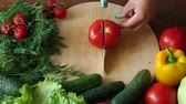 vegetarianismo : Close-up of a woman chef cuts a ripe tomato on a wooden chopping Board. Slow motion.