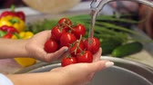cerise rouge : Close-up of a young girl washing ripe cherry tomatoes in the sink at home, cooking dinner or lunch at home. High resolution.