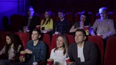 кино : Young people sitting at the cinema, watching a movie and eating pop corn. Close-up. Entertainment and enjoyment concept.