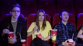 lugares sentados : Young fashionable teenagers sit in the cinema and watch a Comedy or a melodrama, eat popcorn and drink Cola. Portrait of smiling teenagers in a modern cinema.