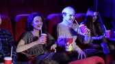 commedia : Friendly family with interest watching a movie and eating popcorn in the cinema. Friends watching movie and smiling together. Concept of entertainment and movie time. Side view. Filmati Stock