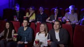 commedia : Close-up of a group of very cheerful friends in the cinema, they watch a Comedy film and laugh a lot. Teenagers laugh at a joke in the movie, they sit in the cinema and eat popcorn.