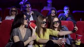 commedia : Three young girls teenagers in 3D glasses take selfies in the cinema. A group of friends are holding popcorn having fun with the phone and taking selfies in the cinema.