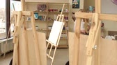 Portrait of a dreamy young girl artist in the Studio for drawing. Girl artist in a white shirt with bright makeup and red lipstick, she walks around the drawing Studio among easels and paintings. 動画素材