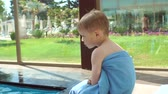 strandlaken : Little blond boy wrapped in a towel after swimming in the pool. The child is frozen in the pool water, it is covered with a towel and heated after bathing. Slow motion.