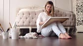 flower bed : Sexy girl in ripped jeans and white blouse draws at home sitting on the floor near the bed. Slow motion. Stock Footage