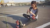 blading : attractive hipster female fix roller skates on the street at sunset